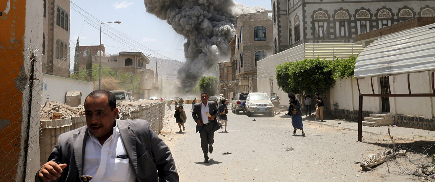 People flee as smoke billows after air strikes hit the house of Yemen's former President Ali Abdullah Saleh in Sanaa May 10, 2015. Saleh and his family are safe after airstrikes targeted his residence in the capital Sanaa early on Sunday, a news agency allied to the former Yemeni president said. REUTERS/Mohamed al-Sayaghi/File photo