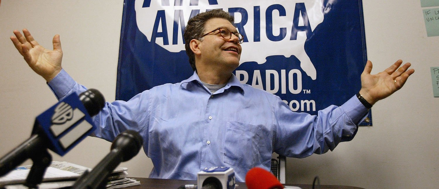 """Political satirist Al Franken speaks during a news conference at Air America Radio studios August 25, 2004 in New York City. Franken urged New Yorkers and Americans across the country who are opposed to the Bush presidency to open their windows and shout the moment the President takes the stage in New York to deliver his address to the National Republican Convention. Dubbed the """"Great American Shout-Out"""", Franken is urging New Yorkers to yell """"Fuggedaboutit"""", a play on the phrase """"Forget about it."""" (Photo by Spencer Platt/Getty Images)"""