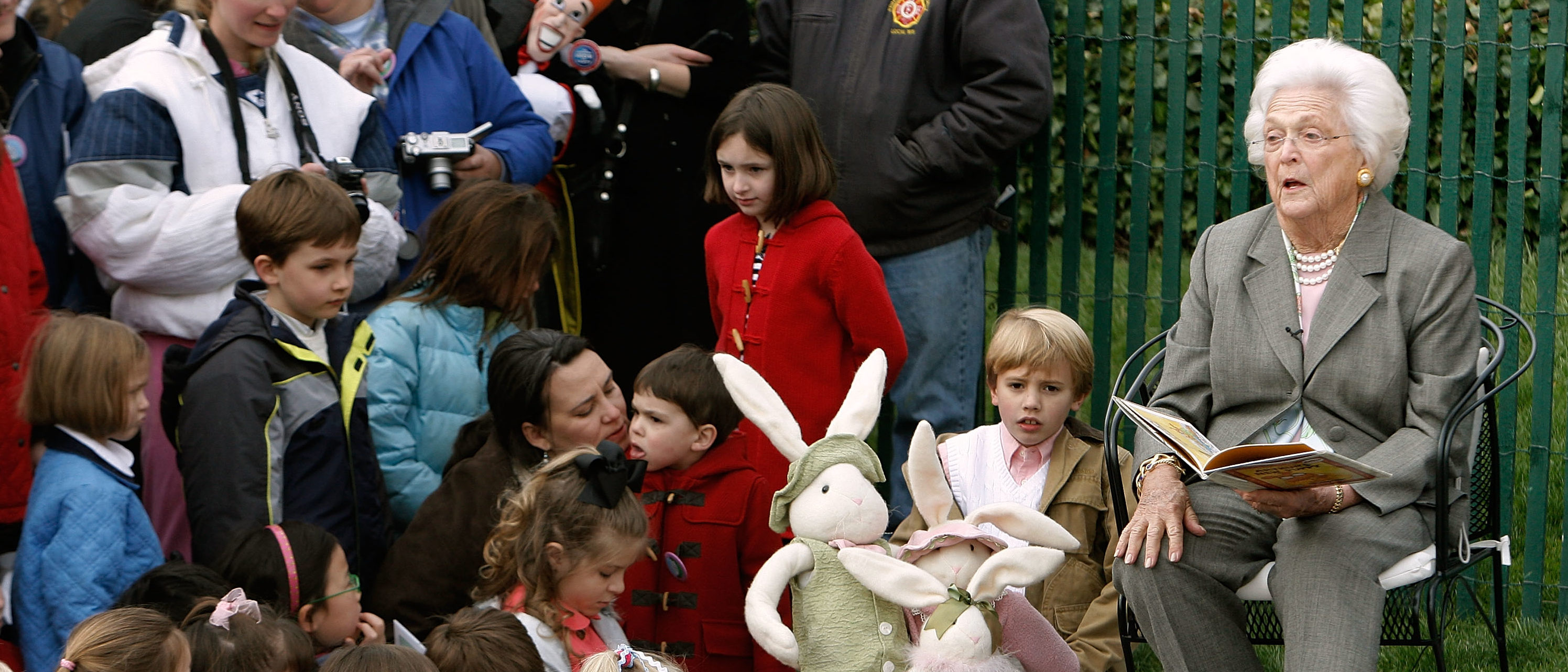 """WASHINGTON - MARCH 24: Former first lady and mother of President George W. Bush, Barbara Bush (R) reads """"Arthur's New Puppy"""" during the annual Easter Egg Roll on the South Lawn of the White House March 24, 2008 in Washington, DC. The annual event was started by President Rutherford B. Hayes in 1878. (Photo by Chip Somodevilla/Getty Images)"""