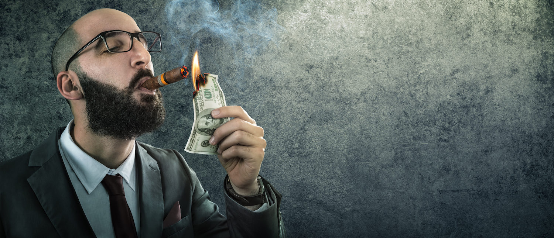 Arrogant businessman burning money. (Shutterstock/Romolo Tavani) | HUD Let $2 Billion Go To Barred People