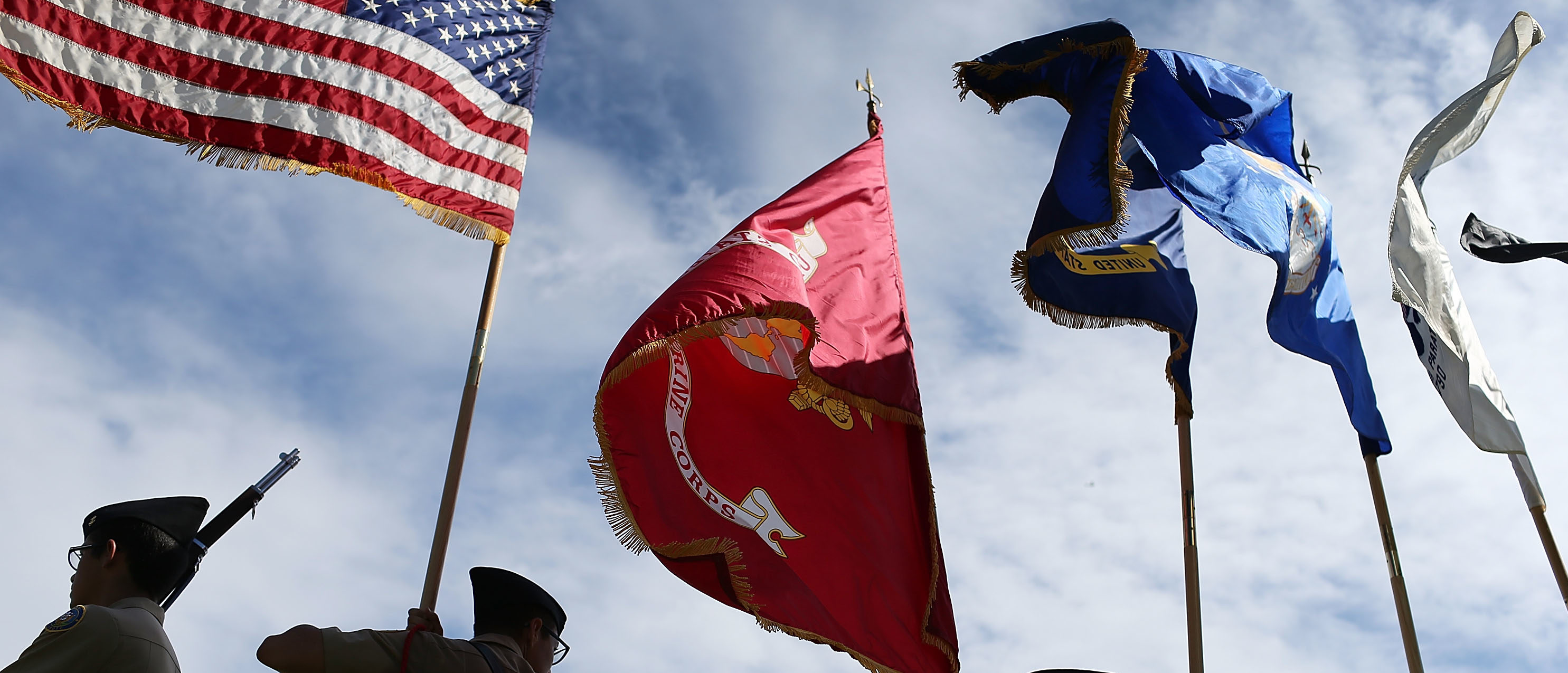 MIAMI BEACH, FL - NOVEMBER 11: Members of the G. Holmes Braddock Senior High School NJROTC color guard carry their flags during a Veterans day ceremony on November 11, 2015 in Miami Beach, Florida. Originally established as Armistice Day in 1919, the holiday was renamed Veterans Day in 1954 by President Dwight Eisenhower, and honors those who have served in the U.S. military. (Photo by Joe Raedle/Getty Images)