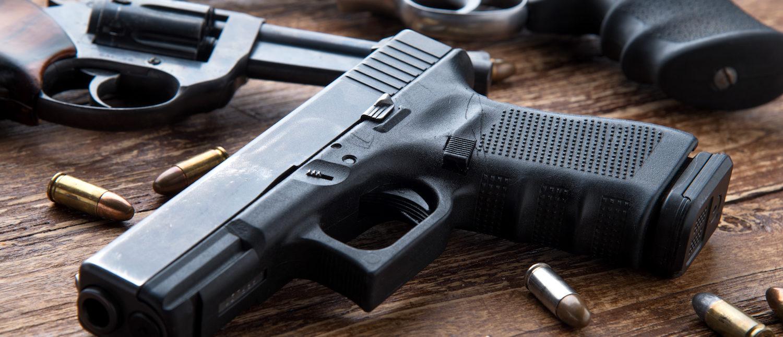 Gun with ammunition on wooden background. (Shutterstock/Kiattipong)