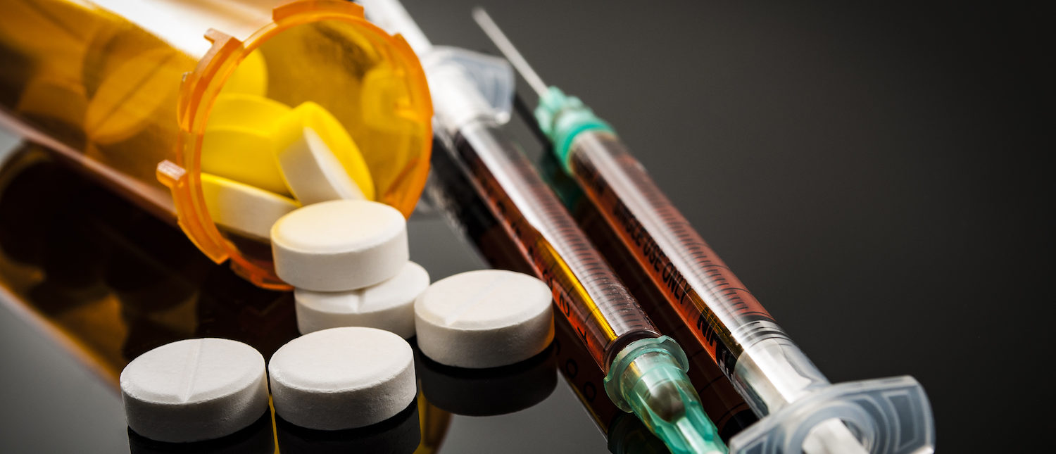 Opioid epidemic, drug abuse concept with closeup on two heroin syringes or other narcotics surrounded by scattered prescription opioids. Oxycodone is the generic name for a range of opioid painkillers. (Shutterstock/Victor Moussa) | New DEA Rule Combats Black Market Opioids