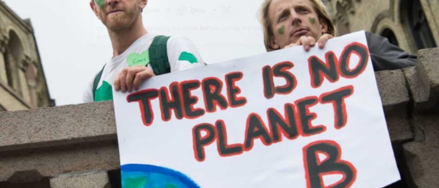 """OSLO - SEPTEMBER 21: Men hold a sign reading, """"There Is No Planet B"""", as thousands march through downtown Oslo, Norway, to support action on global climate change, September 21, 2014. Ryan Rodrick Beiler/Shutterstock.com)  """