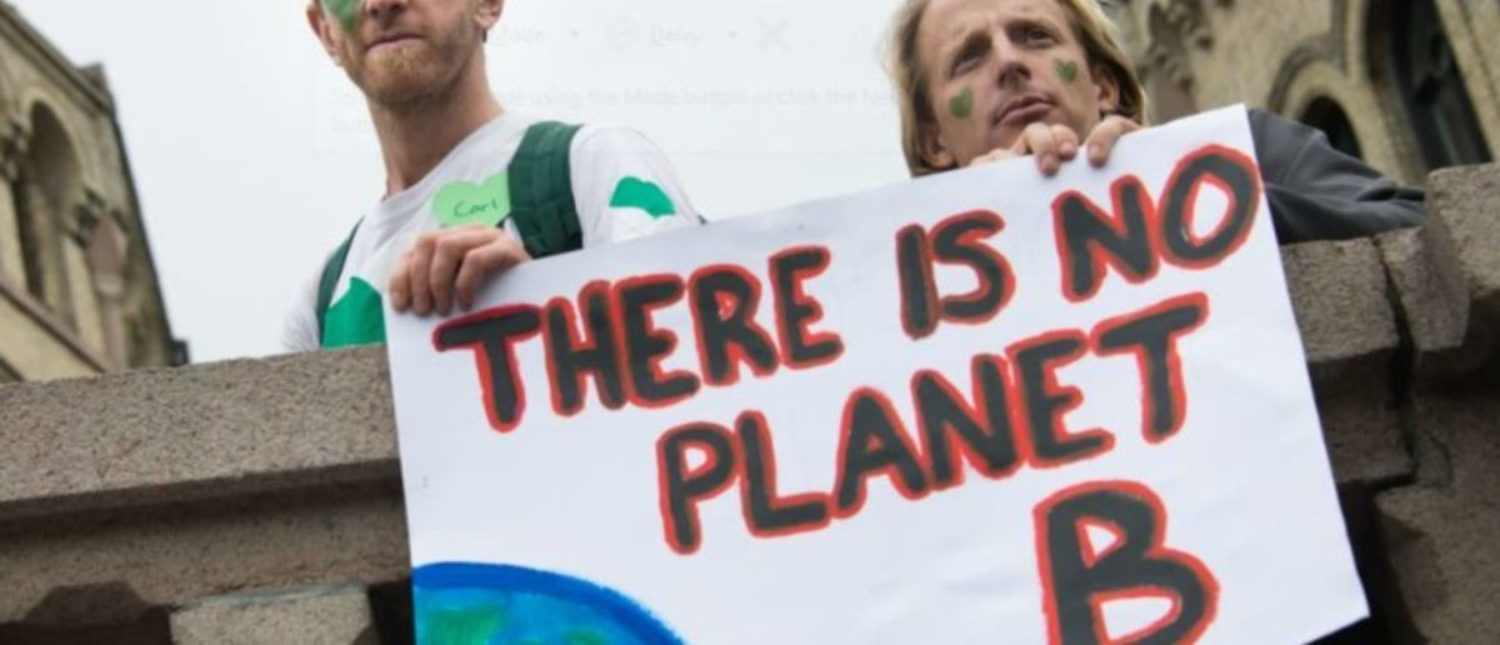"""OSLO - SEPTEMBER 21: Men hold a sign reading, """"There Is No Planet B"""", as thousands march through downtown Oslo, Norway, to support action on global climate change, September 21, 2014. Ryan Rodrick Beiler/Shutterstock.com 