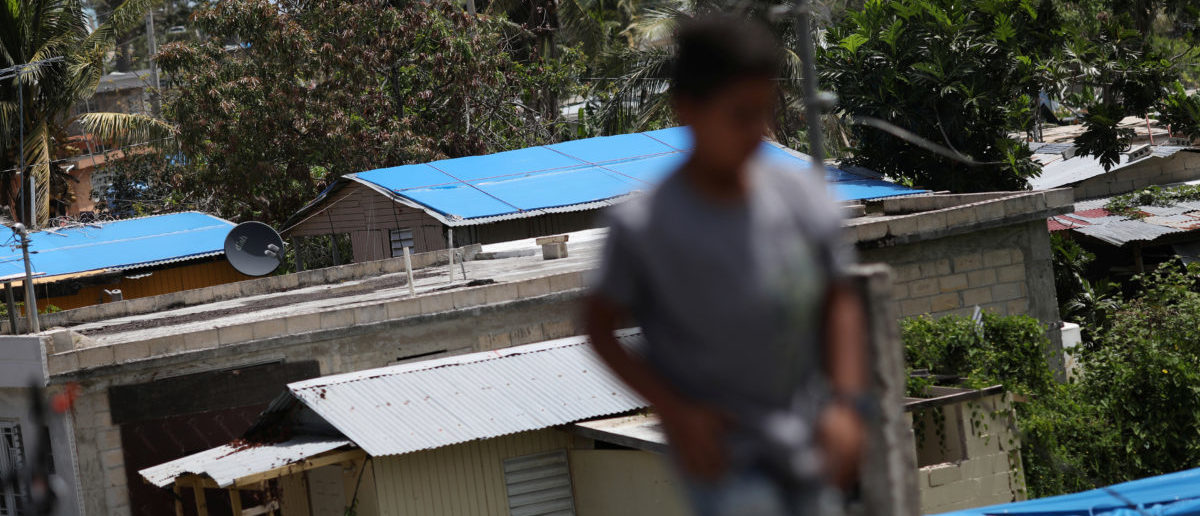 A boy walks near houses with plastic sheets replacing roofs hit by Hurricane Maria in September, in a neighbourhood in Canovanas, Puerto Rico April 10, 2018. REUTERS/Alvin Baez