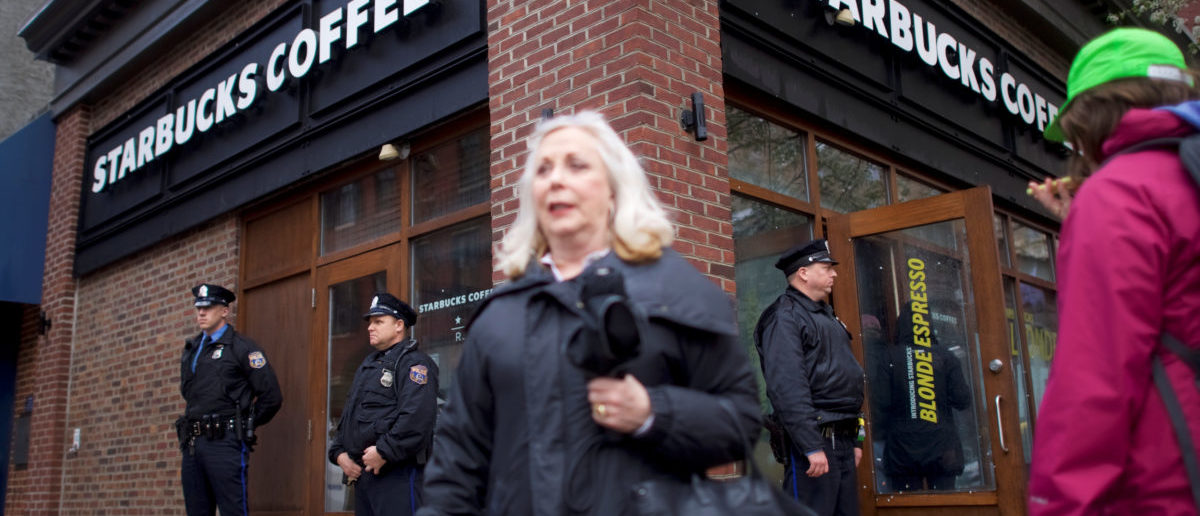 Police officers monitor activity outside as protestors demonstrate inside a Center City Starbucks, where two black men were arrested, in Philadelphia, Pennsylvania U.S. April 16, 2018.  REUTERS/Mark Makela