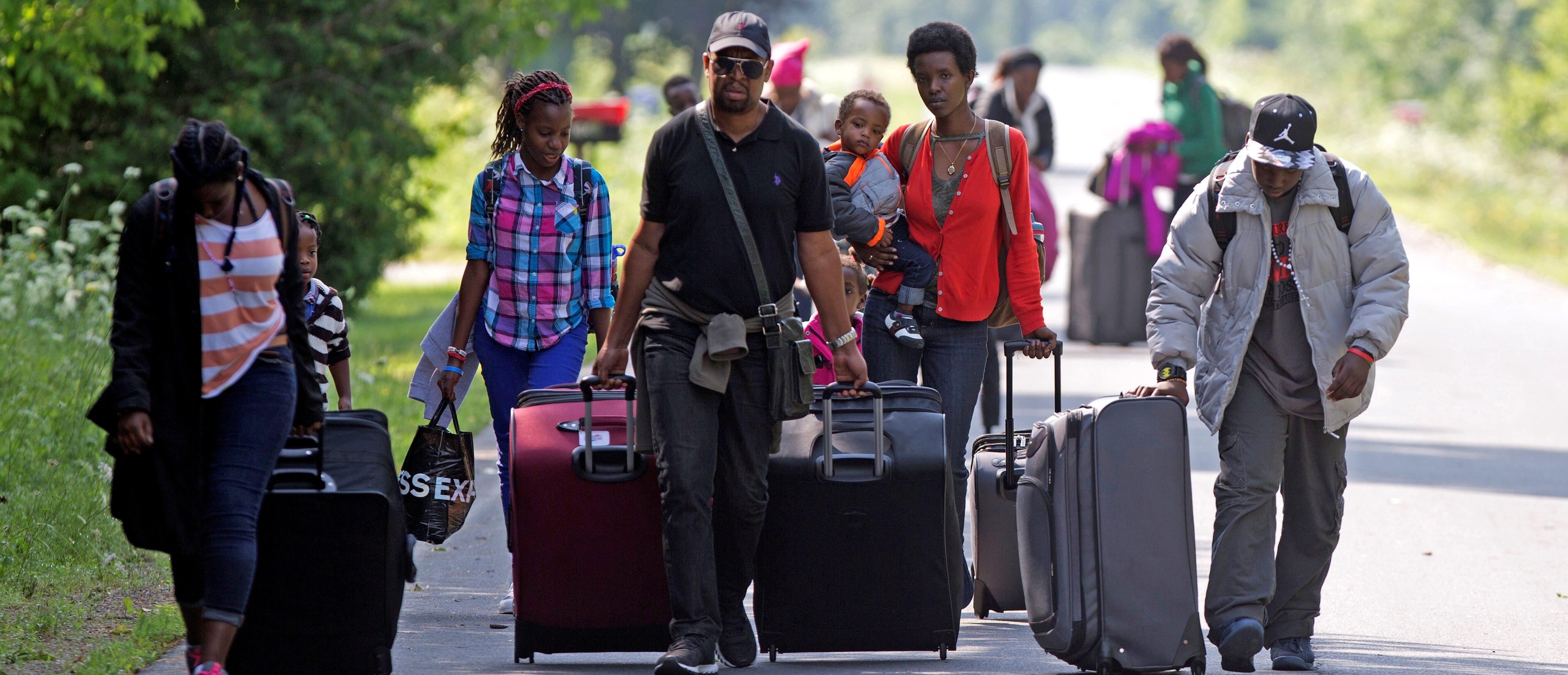 FILE PHOTO: Three families that claimed to be from Burundi walk down Roxham Road to cross into Quebec at the US-Canada border in Champlain, New York, August 3, 2017. REUTERS/Christinne Muschi/File Photo