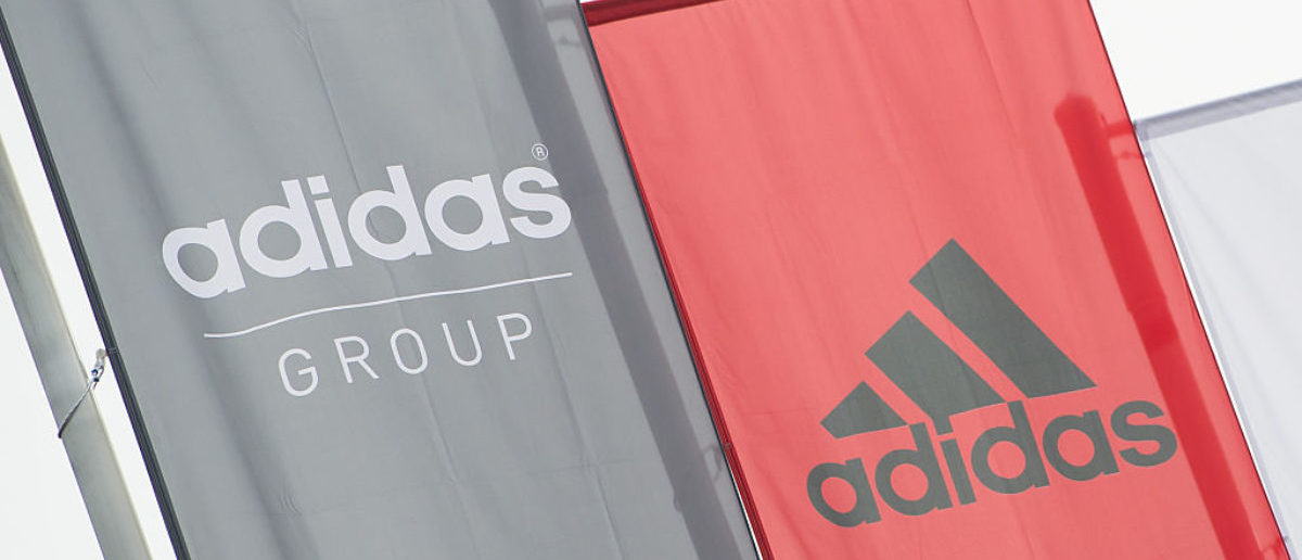 The logo of German sport brand Adidas is pictured on waving flags in front of the Adidas Headquarter in Herzogenaurach on January 25, 2016. / AFP / LUKAS BARTH (Photo credit should read LUKAS BARTH/AFP/Getty Images)