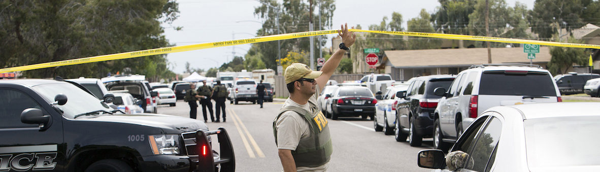 An FBI agent lifts police tape at one of the scenes of a multiple location shooting that has injured at least four people in Mesa, Arizona March 18, 2015. One person was killed and five others wounded when a gunman opened fire on Wednesday at a motel and at least three other locations across the Phoenix suburb of Mesa, police said.  REUTERS/Deanna Dent  (UNITED STATES - Tags: CRIME LAW) - GM1EB3J0DMO01