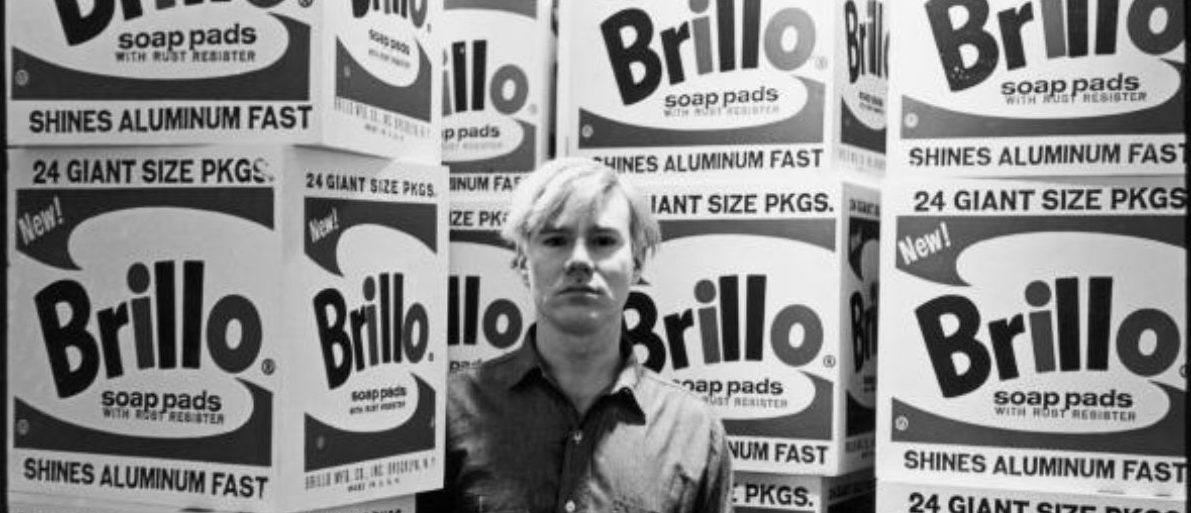 American pop artist Andy Warhol (1928 - 1987) stands amid his towering Brillo box sculptures in the Stable Gallery (33 East 74th Street), New York, New York, April 21, 1964. (Photo by Fred W. McDarrah/Getty Images) | Museum Auctioning Off Warhol Paintings