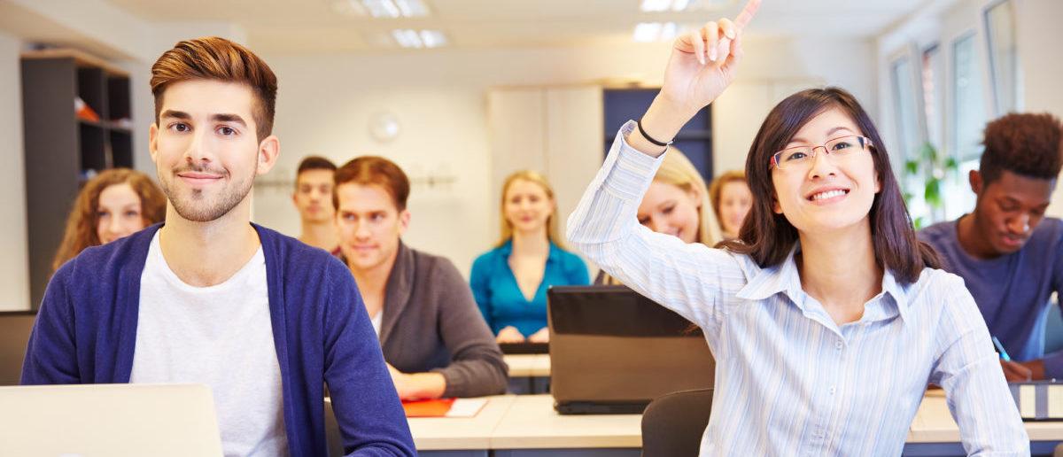 Asian student raising her hand in a university classroom - ShutterStock -- Robert Kneschke | Teacher Tries To Give Girls Higher Grades