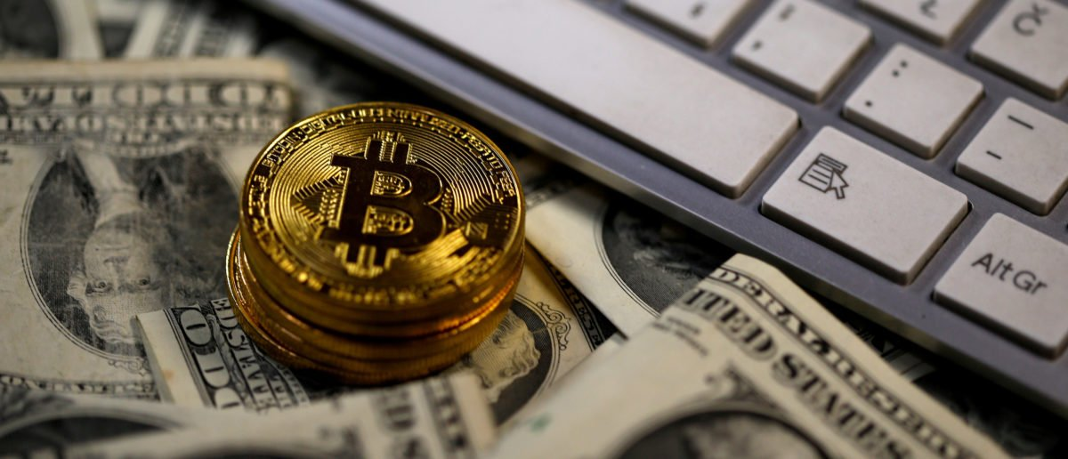 FILE PHOTO: Bitcoin (virtual currency) coins placed on Dollar banknotes, next to computer keyboard, are seen in this illustration picture, November 6, 2017. REUTERS/Dado Ruvic/Illustration/File Photo - RC1E4411F600
