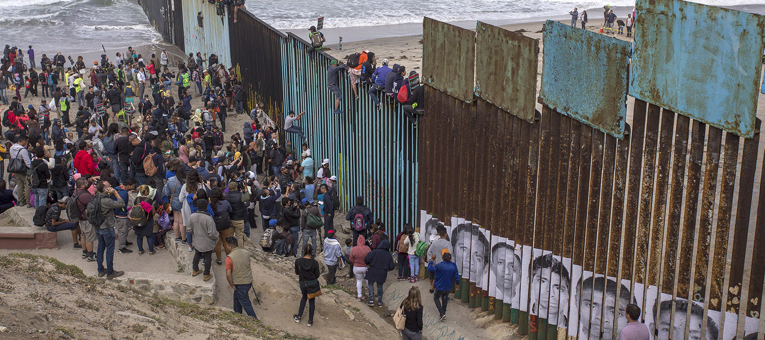 People climb a section of border fence to look into the U.S. as members of a caravan of Central American asylum seekers arrive to a rally on April 29, 2018 in Tijuana, Baja California Norte, Mexico. More than 300 immigrants, the remnants of a caravan of Central Americans that journeyed across Mexico to ask for asylum in the United States, have reached the border to apply for legal entry. (Photo by David McNew/Getty Images)
