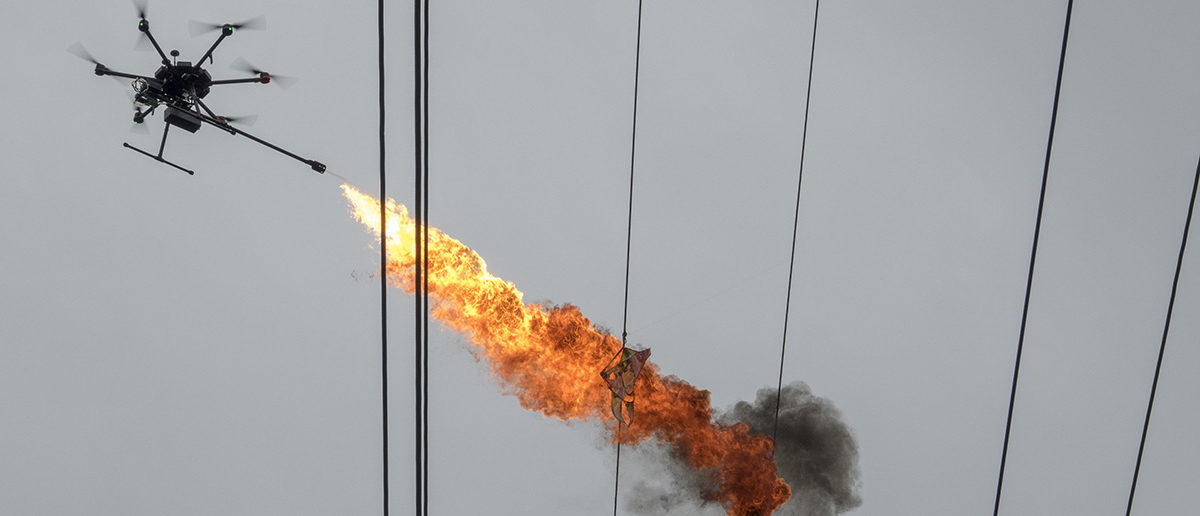 A drone operated by staff of Hainan Power Grid Corporation emits flame to burn down trash from power lines, in Haikou, Hainan province, China November 16, 2017. Picture taken November 16, 2017. REUTERS/Stringer ATTENTION EDITORS - THIS IMAGES WAS PROVIDED BY A THIRD PARTY. CHINA OUT. TPX IMAGES OF THE DAY -