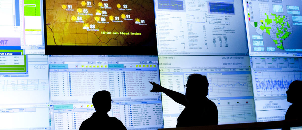 Reliability Coordinators Wes Watkins and Kim Engram and Steven Andrews monitor the state power grid during a tour of the Electric Reliability Council of Texas (ERCOT) command center in Taylor