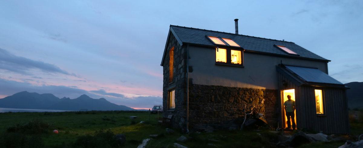Ben Cormack stands in the doorway of his home on the Isle of Eigg, Inner Hebrides, Scotland