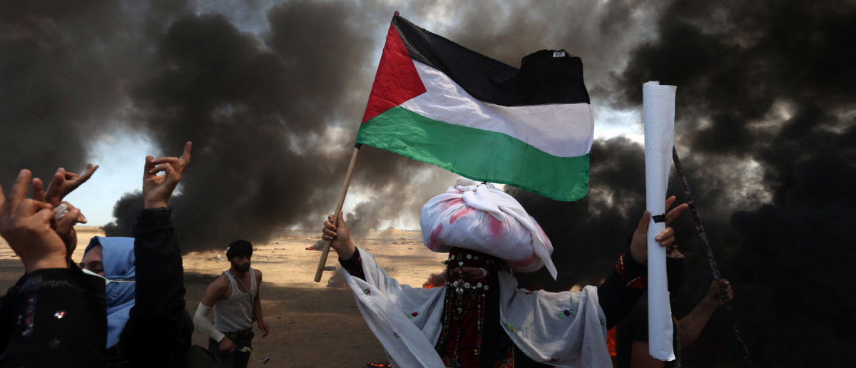 A female demonstrator holds a Palestinian flag during a protest against U.S. embassy move to Jerusalem and ahead of the 70th anniversary of Nakba, at the Israel-Gaza border in the southern Gaza Strip May 14, 2018. REUTERS/Ibraheem Abu Mustafa