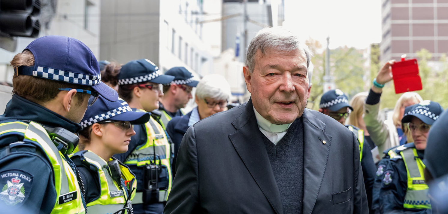 Vatican Treasurer Cardinal George Pell is surrounded by Australian police as he leaves the Melbourne Magistrates Court in Australia, October 6, 2017. REUTERS/Mark Dadswell