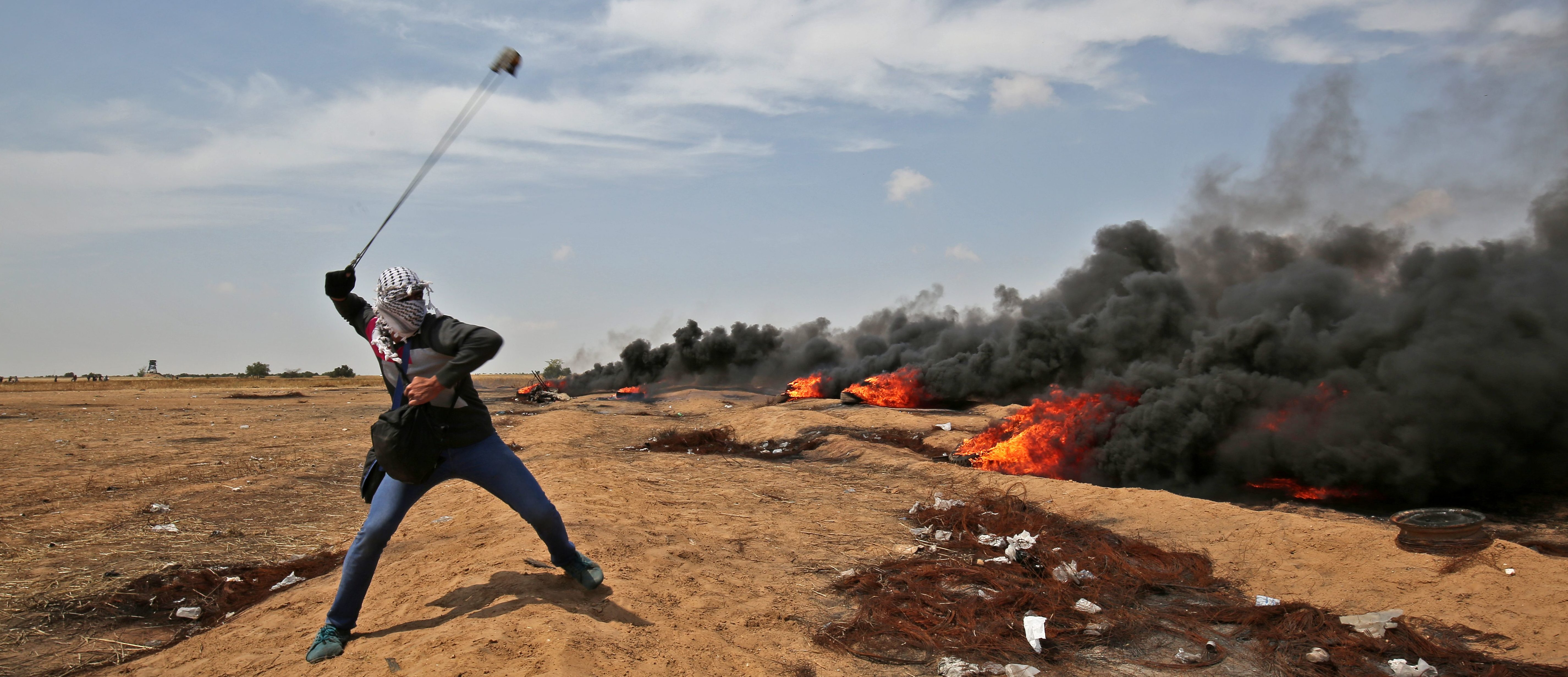 TOPSHOT - A Palestinian demonstrator uses a slingshot to throw stones towards Israeli security forces near the southern Gaza Strip town of Khan Yunis during the fifth straight Friday of mass demonstrations and clashes along the Gaza-Israel border on April 27, 2018. (Photo by SAID KHATIB / AFP) (Photo credit should read SAID KHATIB/AFP/Getty Images)