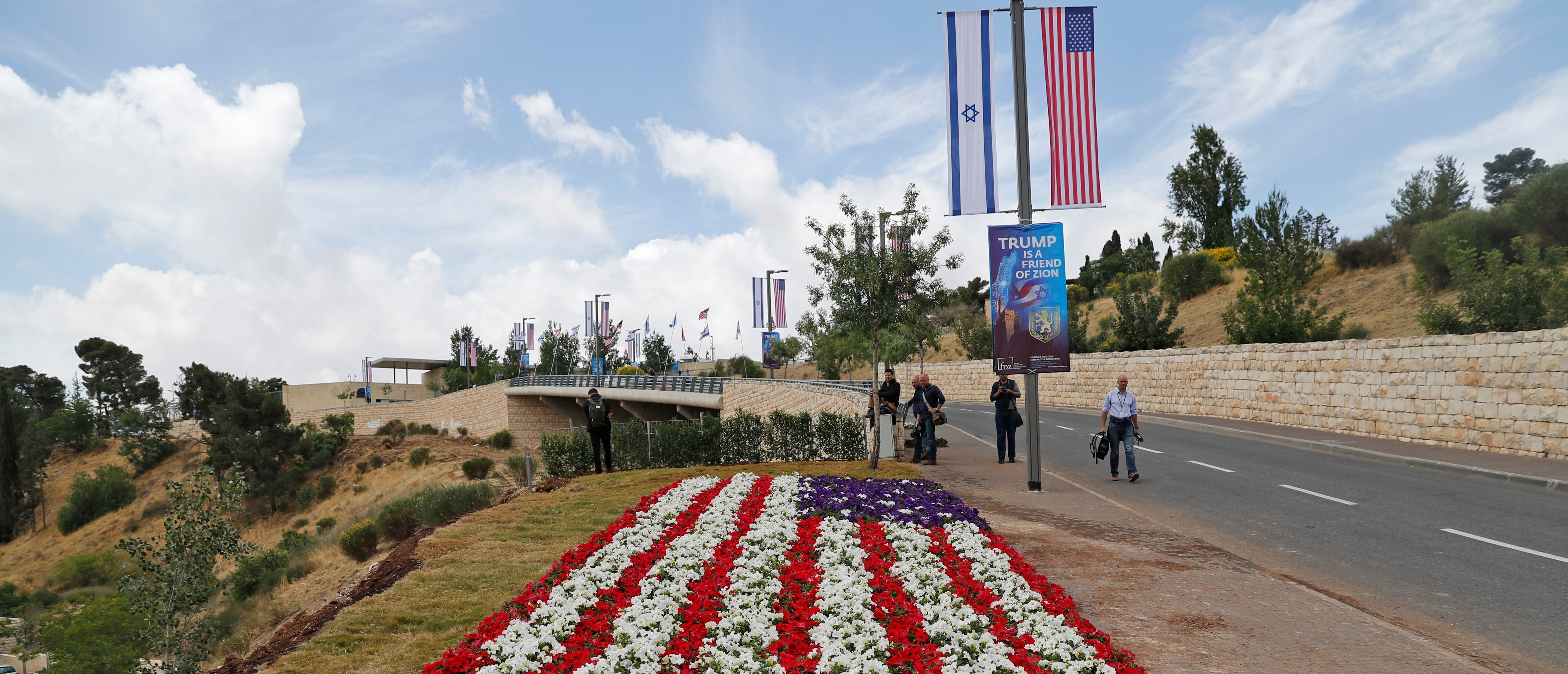 Journalists gather on May 13, 2018, near the compound of the US consulate in Jerusalem, which will host the new US embassy, as posters praising the US president hang in the street. (Photo by Ahmad GHARABLI / AFP) (Photo credit should read AHMAD GHARABLI/AFP/Getty Images)