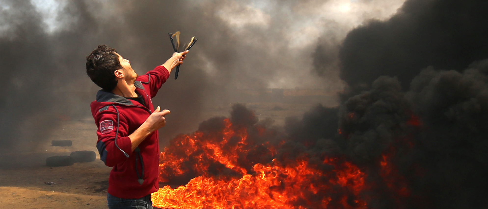A Palestinian man uses a slingshot during clashes with Israeli forces along the border with the Gaza strip east of Khan Yunis on May 14, 2018, as Palestinians protest over the inauguration of the US embassy following its controversial move to Jerusalem. (Photo by SAID KHATIB / AFP) (Photo credit should read SAID KHATIB/AFP/Getty Images
