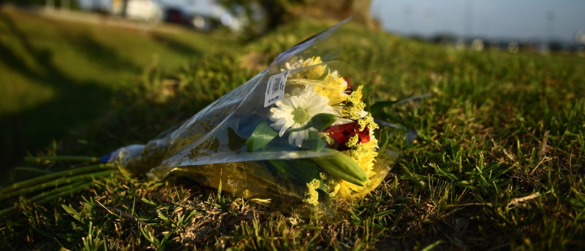 Flowers lie on the ground at Santa Fe High School on May 19, 2018, in Santa Fe, Texas. - Ten people, mostly students, were killed when a teenage classmate armed with a shotgun and a revolver opened fire at the school on May 18. The gunman, arrested on murder charges, was identified as Dimitrios Pagourtzis, a 17-year-old junior at Santa Fe High School. He is being held on capital murder charges, meaning he could face the death penalty. (Photo by Brendan Smialowski / AFP) (Photo credit should read BRENDAN SMIALOWSKI/AFP/Getty Images) | US Suffers Five Shootings In Nine Days