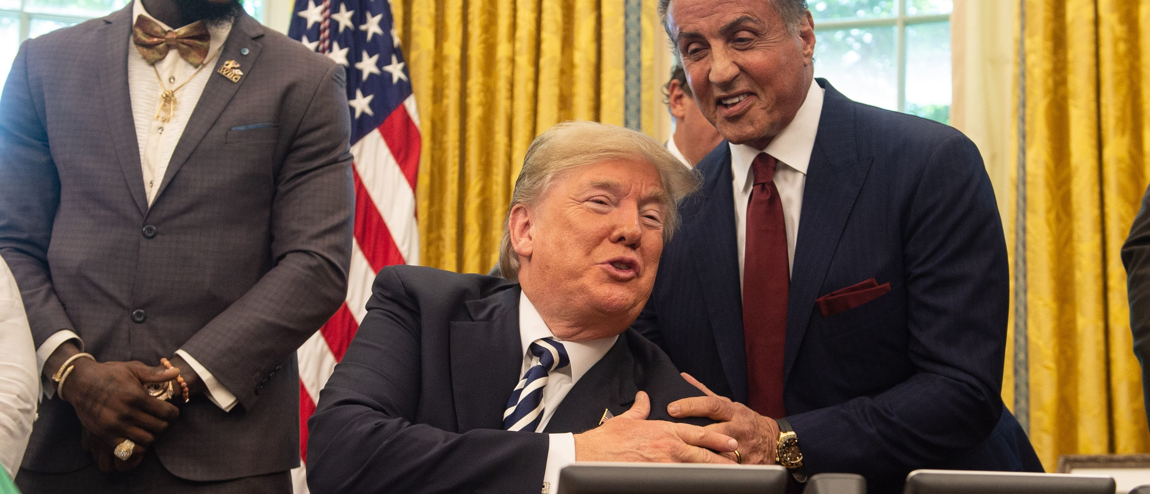 US President Donald Trump jokes with actor Sylvester Stallone(R) before signing a posthumous pardon for former world champion boxer Jack Johnson in the Oval Office at the White House in Washington, DC, on May 24, 2018, as boxer Lennox Lewis looks on. (Photo by NICHOLAS KAMM / AFP) (Photo credit should read NICHOLAS KAMM/AFP/Getty Images)