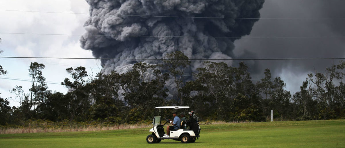 HAWAII VOLCANOES NATIONAL PARK, HI - MAY 15: A man drives a golf cart at a golf course as an ash plume rises in the distance from the Kilauea volcano on Hawaii's Big Island on May 15, 2018 in Hawaii Volcanoes National Park, Hawaii. The U.S. Geological Survey said a recent lowering of the lava lake at the volcano's Halemaumau crater Òhas raised the potential for explosive eruptionsÓ at the volcano. (Photo by Mario Tama/Getty Images)