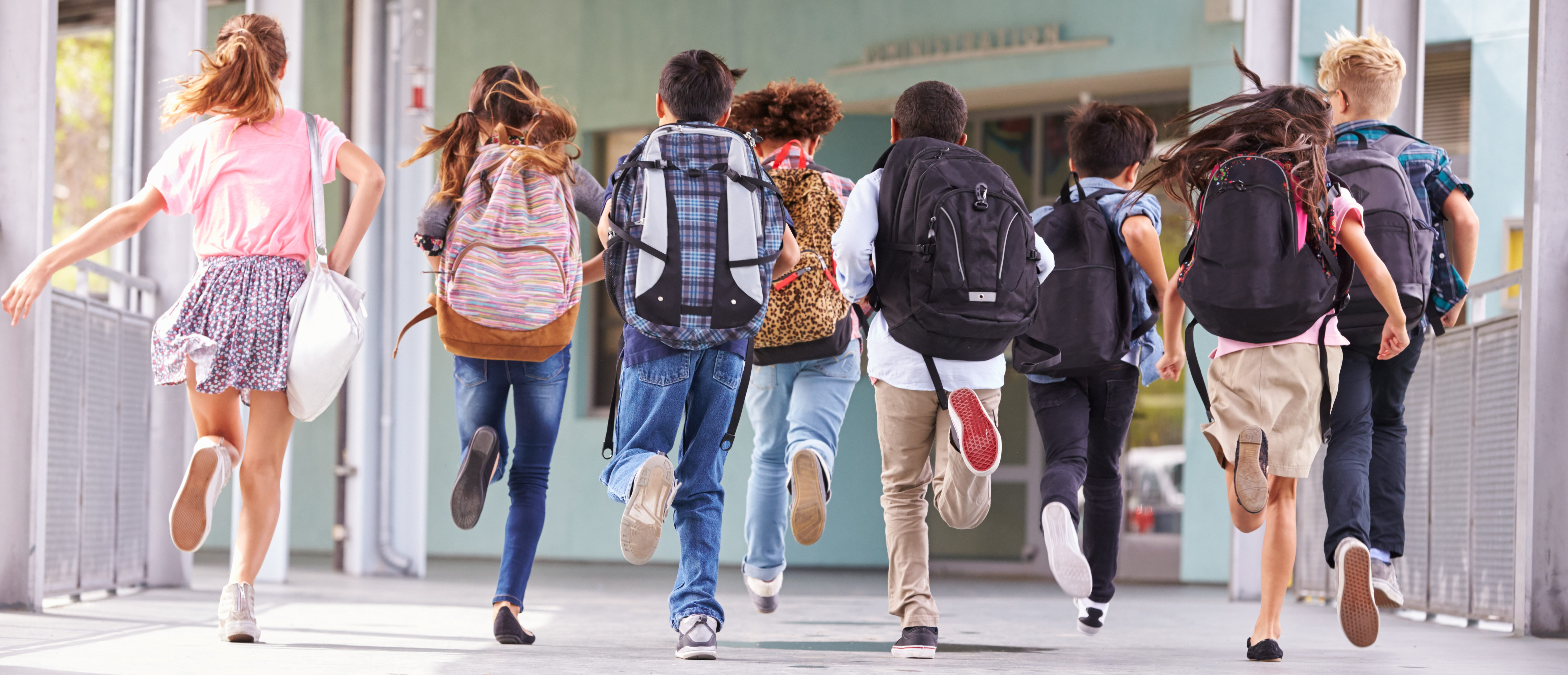 Group of elementary school kids running at school (Shutterstock/ Monkey Business Images)