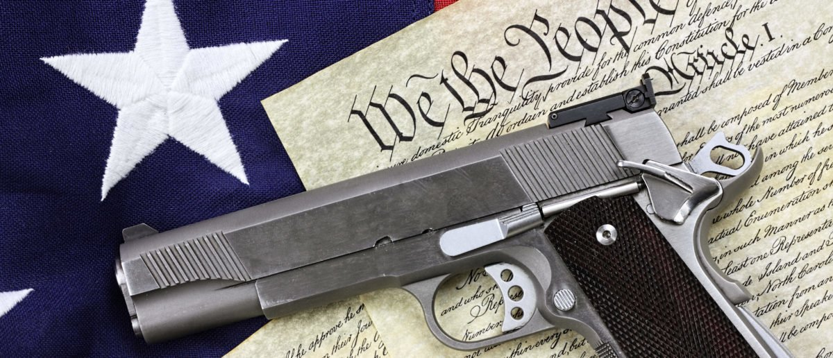 Handgun lying over a copy of the United States constitution and the American flag - ShutterStock Stephanie Frey