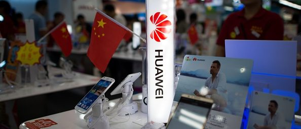 A logo of Huawei Technologies Co Ltd is seen next to a Chinese flag in an electronic shop in Shanghai on October 1, 2014. (Photo: JOHANNES EISELE/AFP/Getty Images)