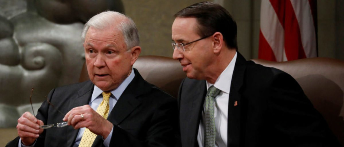 Deputy Attorney General Rod Rosenstein speaks with U.S. Attorney General Jeff Sessions at a summit about combating human trafficking at the Department of Justice in Washington, U.S., February 2, 2018. REUTERS/Aaron P. Bernstein