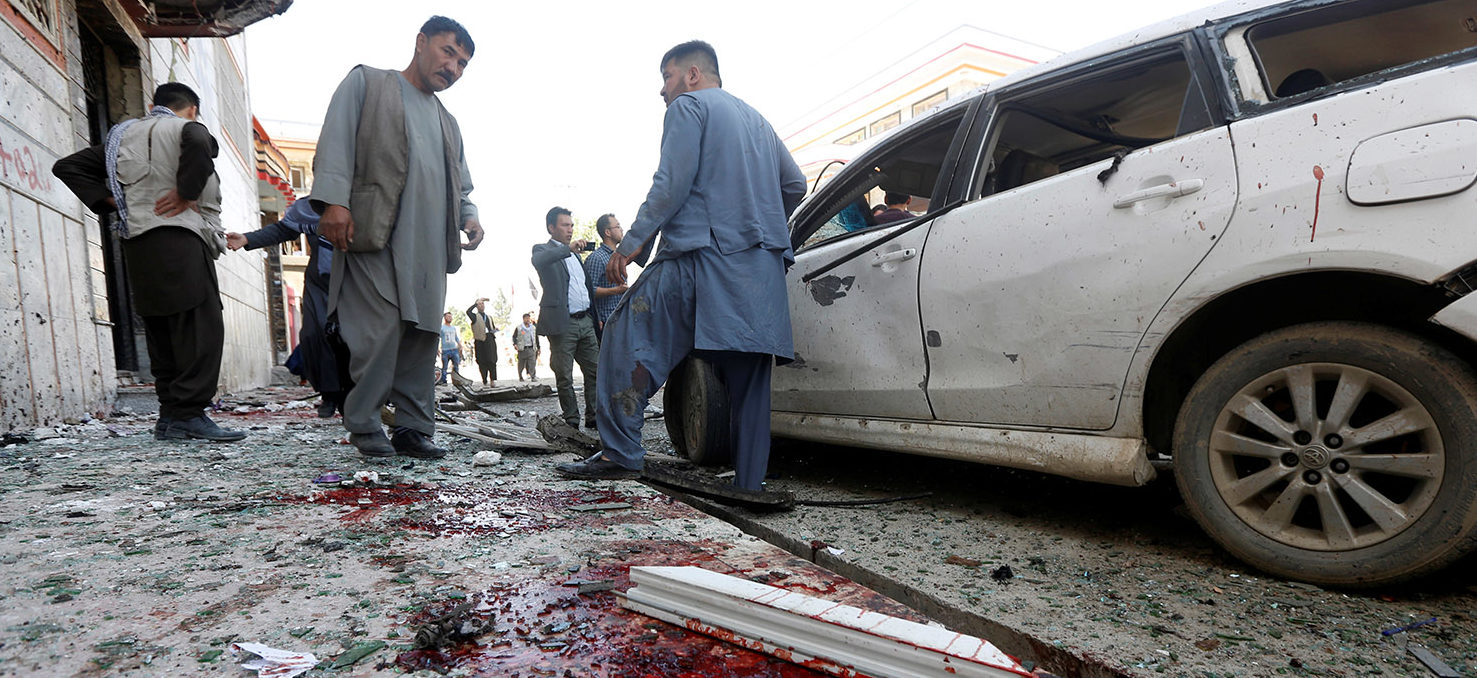 Afghan men inspect the site of a suicide bomb blast in Kabul, Afghanistan April 22, 2018. REUTERS/Omar Sobhani | Bomb Hits Voter Center In Afghanistan