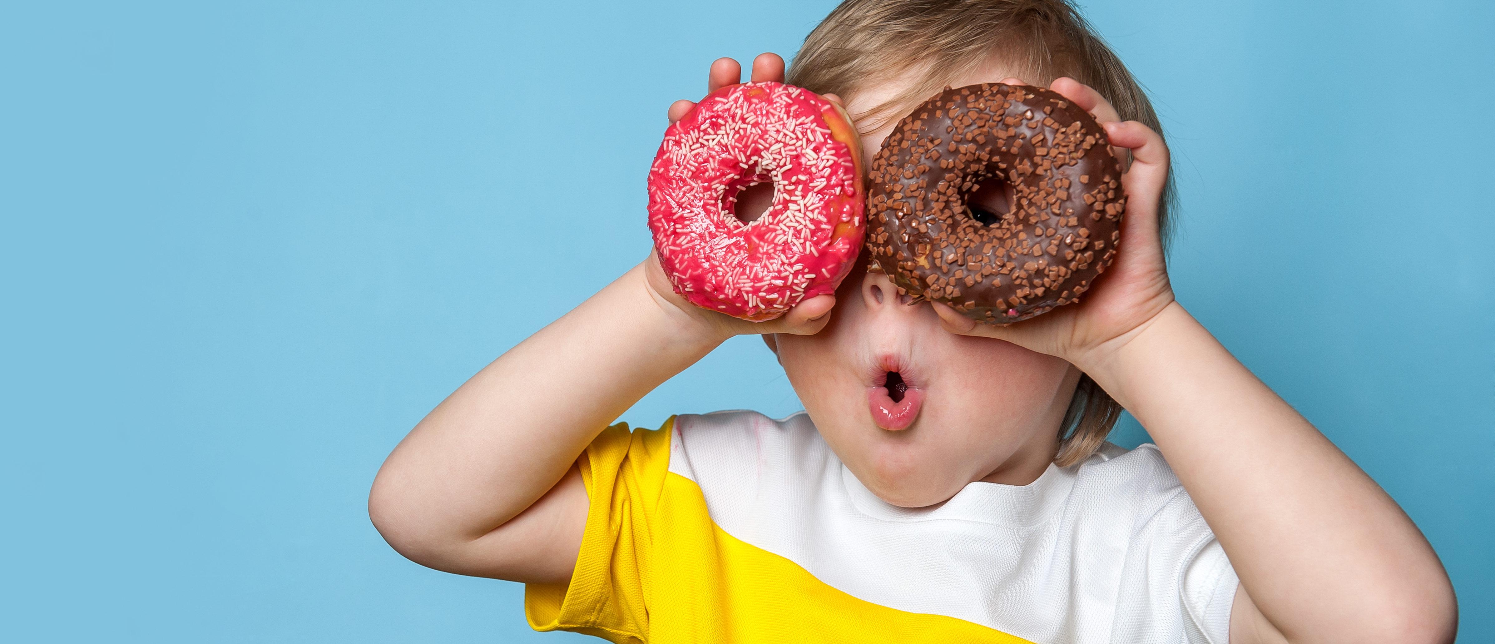 Kid holding donuts (Shutterstock/Sharomka)