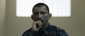 Carlos Tiberio, an imprisoned leader of the Mara MS, listens during a news conference at the high security San Vicente prison in San Vicente April 5, 2013. Several prisoners in representation of the country's two most powerful gangs MS-13 and the 18th Street gang (Mara 18) visited the jail to pledge fellow members of the gangs not to commit violent acts. The pledge is part of a truce between the two gangs which was signed in March 2012 in conjunction with the church, civic organizations and government officials in an effort to reduce violent crimes in the country, according to local media. REUTERS/Ulises Rodriguez