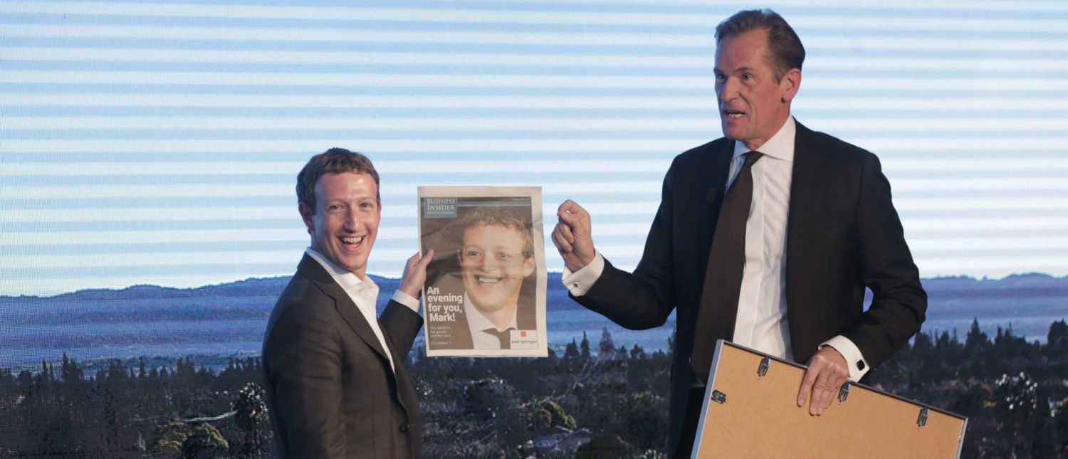 Facebook founder and chief Mark Zuckerberg (L) receives a newspaper from Springer CEO Mathias Doepfner during the Axel Springer Award in Berlin on February 25, 2016. Facebook announced it was donating computer servers to a number of research institutions across Europe, starting with Germany, to accelerate research efforts in artificial intelligence (AI) and machine learning. (Photo: KAY NIETFELD/AFP/Getty Images)   Zuckerberg Rejects Calls To Pay Media