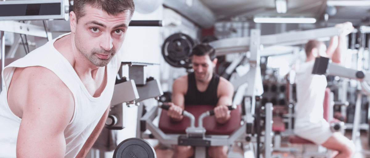 Concentrated sporty guy during workout in gym with dumbbells (Shutterstock/Iakov Filimonov)