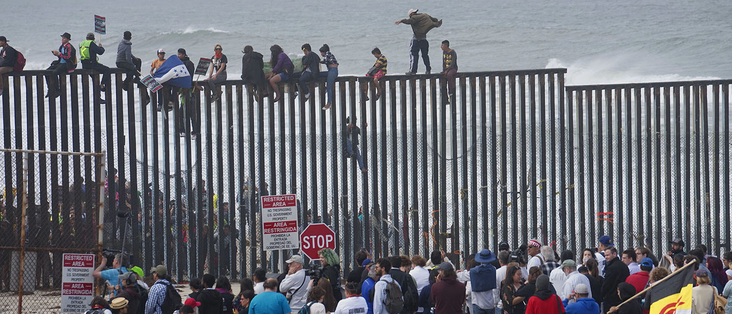 Pro-migrant caravan demonstrators climb the US-Mexico border fence during a rally on April 29, 2018, in San Ysidro, California. - The US has threatened to arrest around 100 Central American migrants if they try to sneak in from the US-Mexico border where they have gathered, prompting US President Donald Trump to order troop reinforcements on the frontier. (Photo by Sandy Huffaker / AFP)