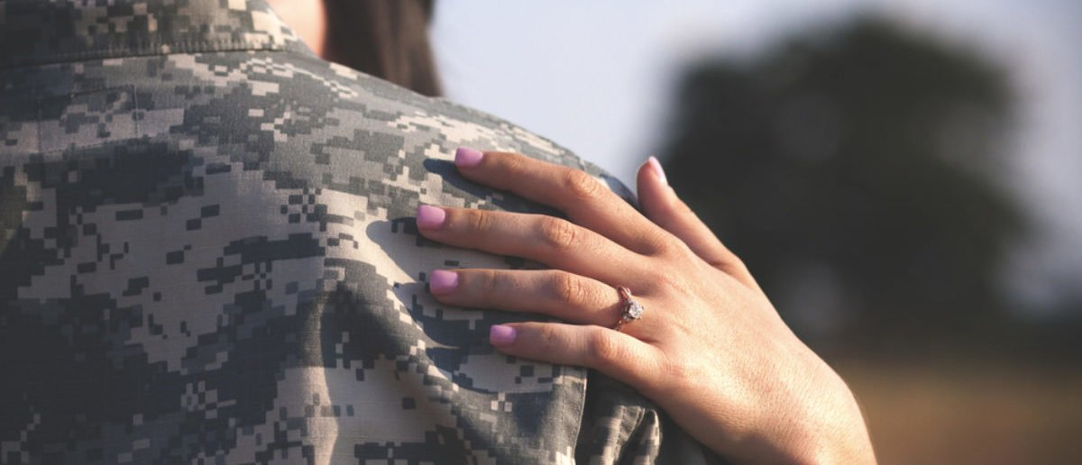 Young military couple kissing in park showing engagement ring (SHUTTERSTOCK: By Sara Nicole Garavuso)