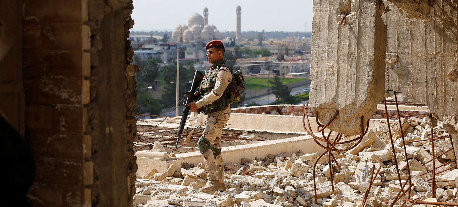 A member of the Iraqi security forces stands guard as Ameen Mukdad, a Mosuli violinist who lived under ISIS's rule for two and a half years where they destroyed his musical instruments, performs at Nabi Yunus shrine in eastern Mosul, Iraq, April 19, 2017. REUTERS/ Muhammad Hamed