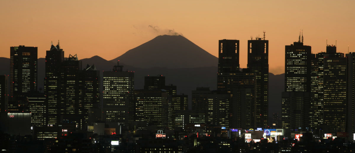 A night view shows Japan's Mt. Fuji seen beyond high-rise buildings in Tokyo February 15, 2007. Japan's economy grew 1.2 percent in October-December from the previous quarter, government data showed on Thursday, beating market expectations, thanks to an upturn in personal consumption. REUTERS/Kim Kyung-Hoon (JAPAN)