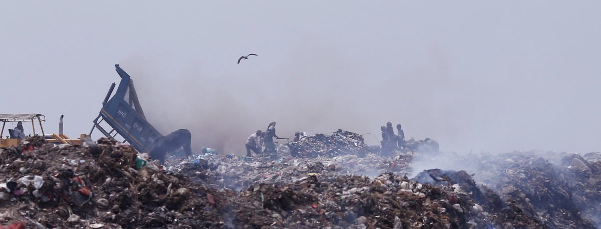 People collect recyclable materials as smoke billows from a burning garbage dump site in New Delhi, India, May 2, 2018. REUTERS/Adnan Abidi