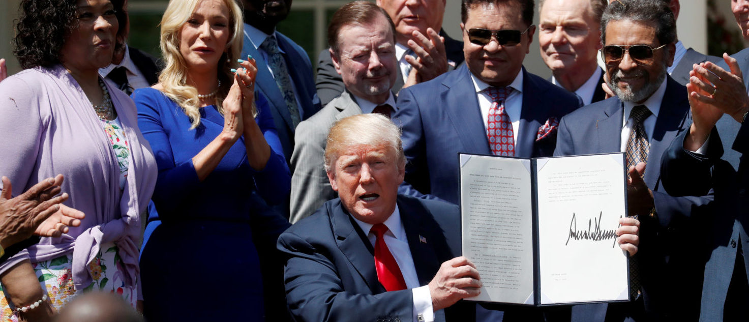 "U.S. President Donald Trump signs an ""Establishment of a White House Faith and Opportunity Initiative"" proclamation after the National Day of Prayer ceremony at the White House in Washington, U.S., May 3, 2018. REUTERS/Leah Millis"