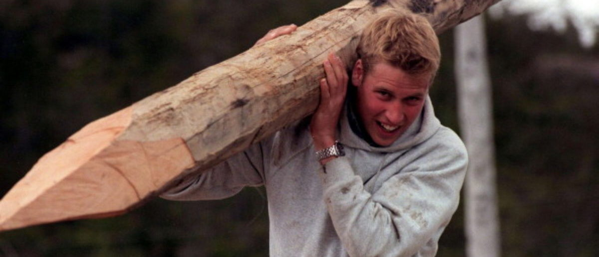 A picture taken in December 2000 of Britain's Prince William carrying a log used to construct walkways linking buildings in the village of Tortel, Southern Chile during his Raleigh International expedition. AFP PHOTO WPA ROTA/TOBY MELVILLE
