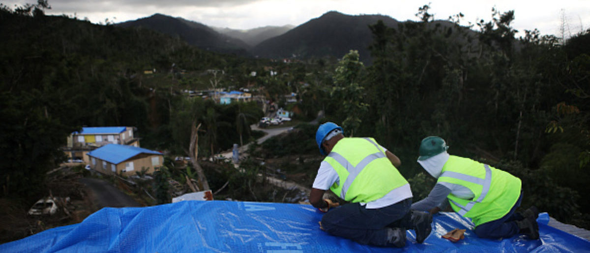Contractors apply a FEMA tarp to a home damaged by Hurricane Maria and without electricity on December 20, 2017 in Morovis, Puerto Rico. (Photo: Mario Tama/Getty Images)