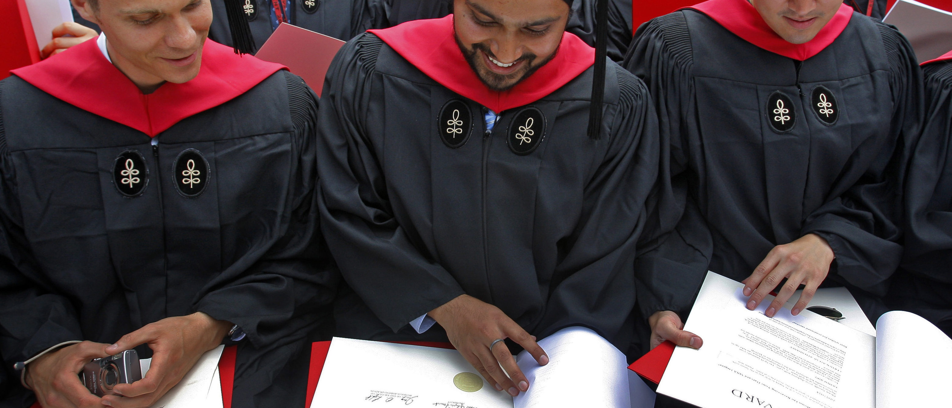 Students look at their diplomas at the Harvard Business School's graduation ceremonies in Boston, Massachusetts following Harvard University's 358th Commencement June 4, 2009. REUTERS/Brian Snyder