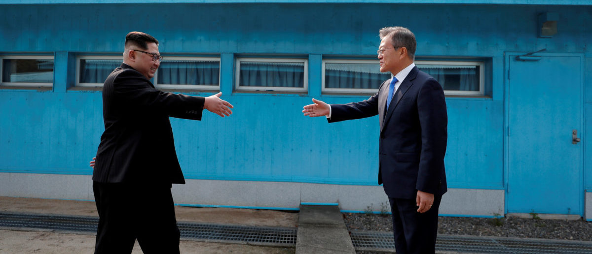 FILE PHOTO: South Korean President Moon Jae-in and North Korean leader Kim Jong Un (L) are about to shake hands on their first ever meeting at the truce village of Panmunjom inside the demilitarized zone separating the two Koreas, South Korea, April 27, 2018.  Korea Summit Press Pool via Reuters/File Photo