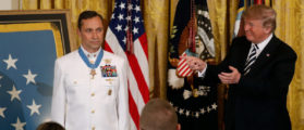 """U.S. President Donald Trump gestures after awarding the Medal of Honor to Retired Navy Master Chief Special Warfare Operator (Sea, Air, and Land) Britt Slabinski for """"conspicuous gallantry"""" in the East Room of the White House in Washington, U.S., May 24, 2018. REUTERS/Kevin Lamarque - RC151A140A30"""