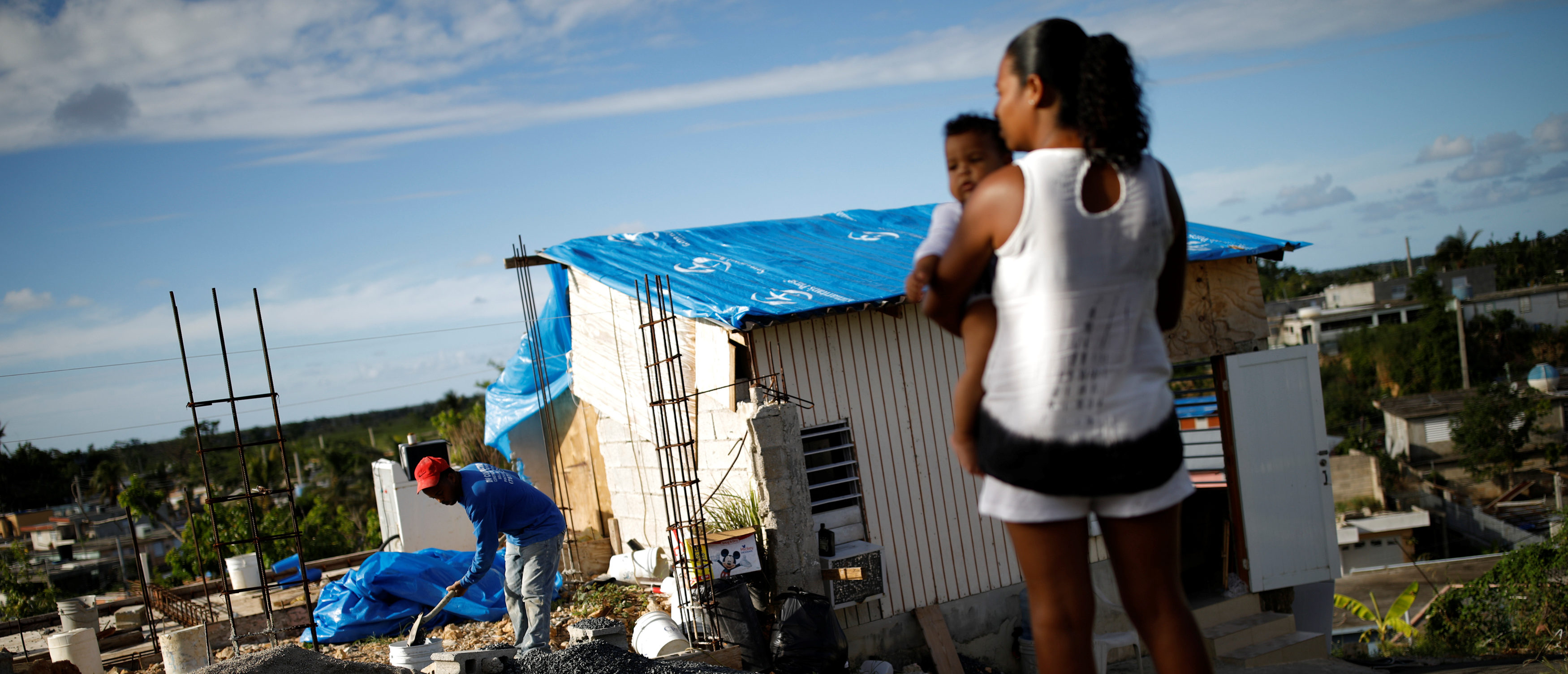 """Samuel Vasquez rebuilds his house, which was partially destroyed by Hurricane Maria, while his wife Ysamar Figueroa looks on, whilst carrying their son Saniel, at the squatter community of Villa Hugo in Canovanas, Puerto Rico, December 11, 2017. Villa Hugo is a settlement initially formed by people whose houses were damaged or destroyed by Hurricane Hugo in 1989. REUTERS/Carlos Garcia Rawlins SEARCH """"RAWLINS HUGO"""" FOR THIS STORY. SEARCH """"WIDER IMAGE"""" FOR ALL STORIES. - RC110A1126A0"""